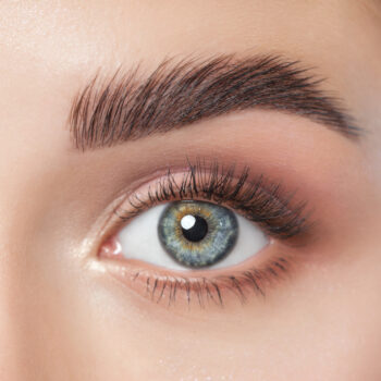 Beautiful woman with long eyelashes, beautiful make-up and thick eyebrows. Beautiful blue eyes close up. Looking at the camera. Cosmetology concept